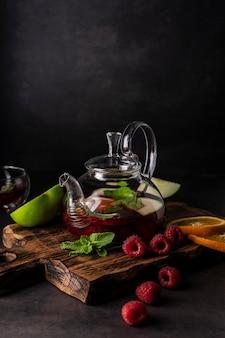 Селективный фокус, свежезаваренный чай в прозрачном чайнике, с фруктами и свежими ягодами. листовой чай и специи. натюрморт. для рекламы и меню