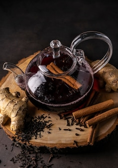 Selective focus, freshly brewed tea in a transparent teapot, with fruits and fresh berries. leaf tea and spices. still-life. for advertising and menus