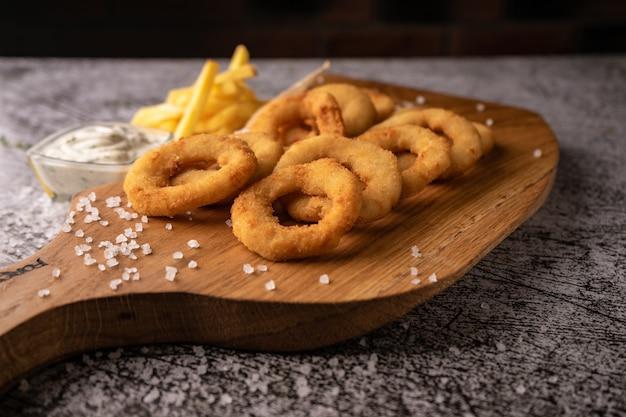 セレクティブフォーカス。油で揚げたパン粉で揚げたオニオンリング。ナチュラルソースで。レストランでお召し上がりいただけます。暗い背景に。メニューと広告用