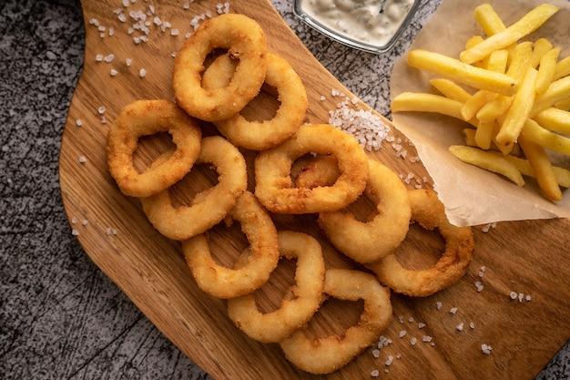 Селективный фокус жареные луковые кольца в панировочных сухарях, обжаренные в масле с натуральным соусом ресторанная подача ...