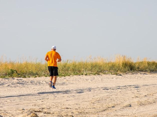 바다를 따라 해변을 따라 달리는 남자 뒤에서 선택적 초점. 여름날 자연에서 스포츠 운동. 운동복을 입은 스포츠 사람들. 건강한 생활.