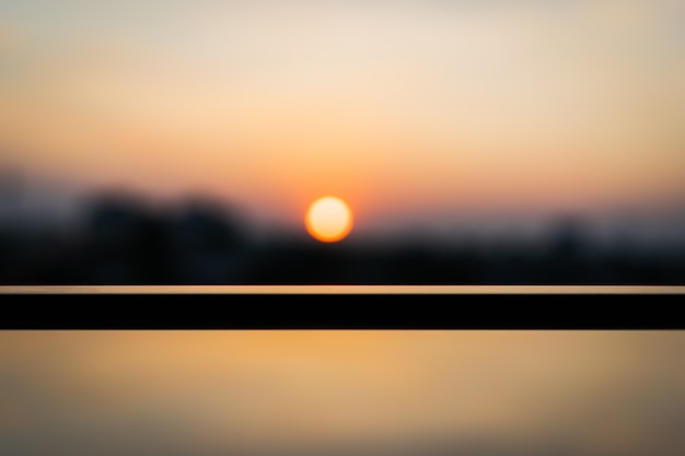 Selective focus of glass table in front of blur sunset view, festival and nature concepts