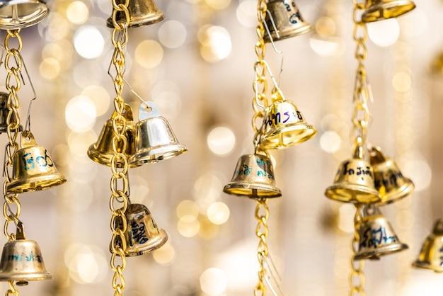 ボケ味の背景を持つ金色のチェーンにぶら下がっている選択的な焦点の金色の鐘