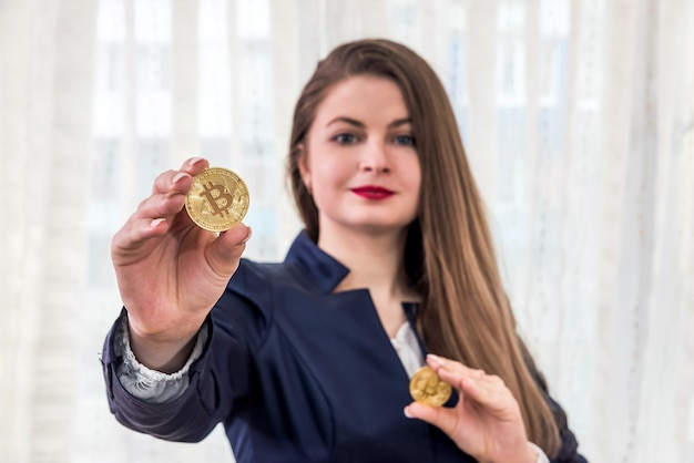 Selective focus on golden bitcoin in woman hands