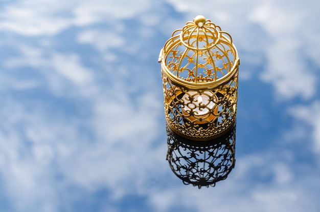 Selective focus of golden lantern with reflection blurred background of cloud and sky for islamic new year concept