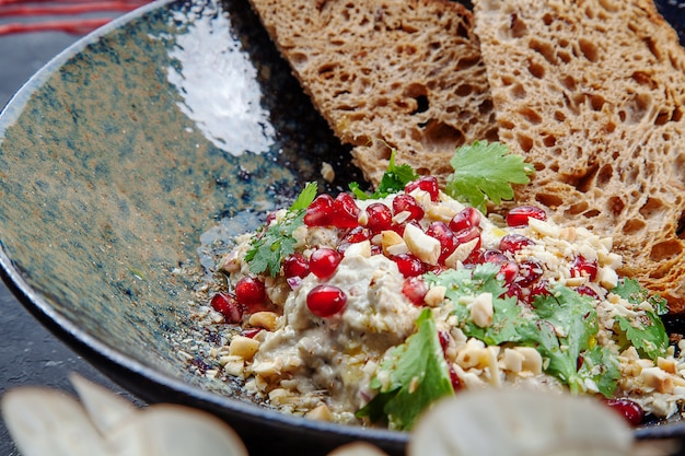 Selective focus grated eggplant in a paste with pomegranate, pine nuts and croutons in dark bowl. healthy, vegan food for lunch. food photo background for menu. eastern cuisine. baba ghanoush