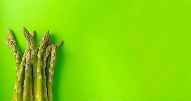 Selective focus, green asparagus pods on a uniform background, vertical position, banner