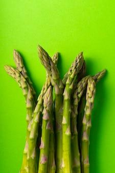 Selective focus, green asparagus pods on a uniform background, vertical position