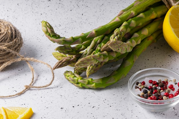 Selective focus, green asparagus pods, on a white background. with lemon slices, spices and basil