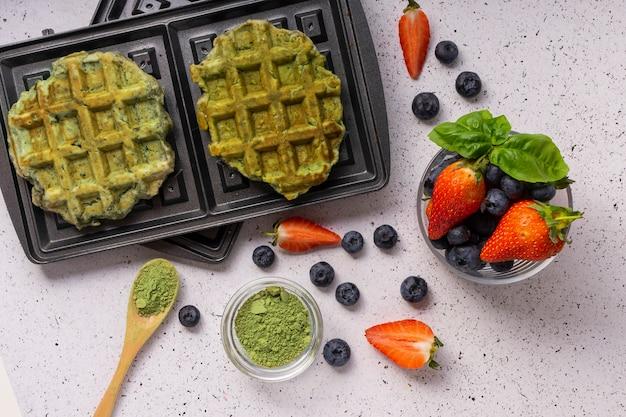 Выборочный фокус, зеленые творожные вафли с матча и свежие ягоды на светлом фоне