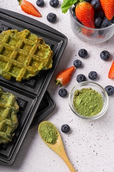 Selective focus, green curd waffles with matcha and fresh berries on a light background