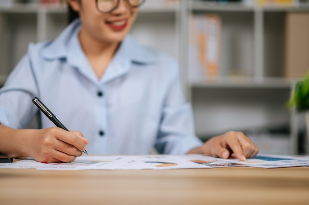 Selective focus hand of asian young woman in eyeglasses use pen working with papers at home office, during quarantine covid-19 self isolation at home, work from home concept