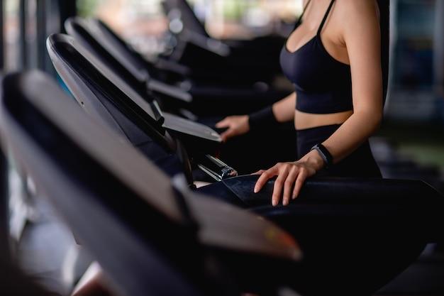 Messa a fuoco selettiva mano di giovane donna sexy che indossa abbigliamento sportivo e smartwatch in piedi sul tapis roulant per allenarsi in palestra moderna, copia spazio