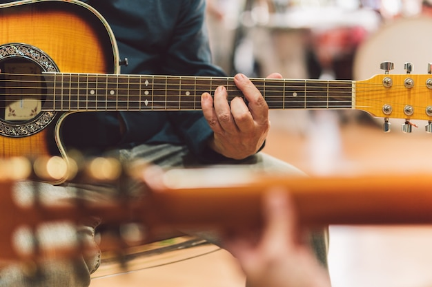 Selective focus on the hands of an older man playing the guitar in duet with a woman.