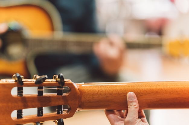 Selective focus on the hands of a woman playing the guitar in duet with a old man.