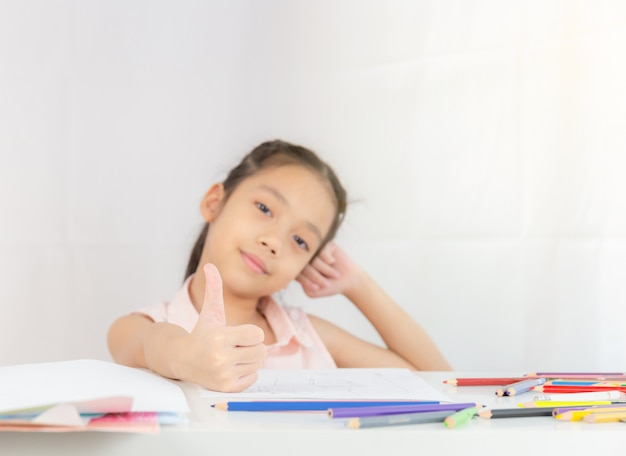 Selective focus of happy little girl kid giving thumb up as sign of success, kid drawing concept