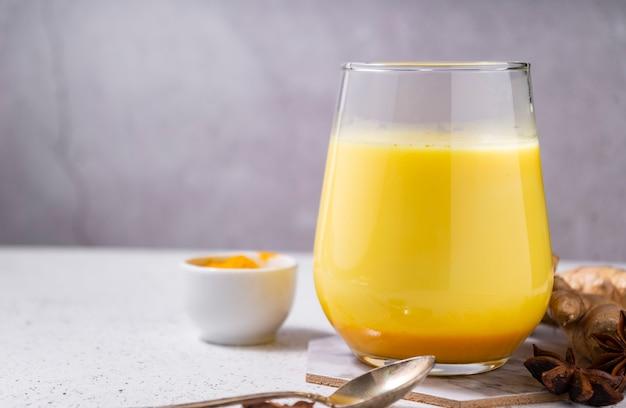 선택적 초점. 건강 한 아유르베 다 음료 골든 아몬드 우유 또는 흰색 바탕에 강황 가루와 호박 심황 라 떼. 복사 공간 채식주의자를위한 향신료와 함께 유행 아시아 천연 해독 음료
