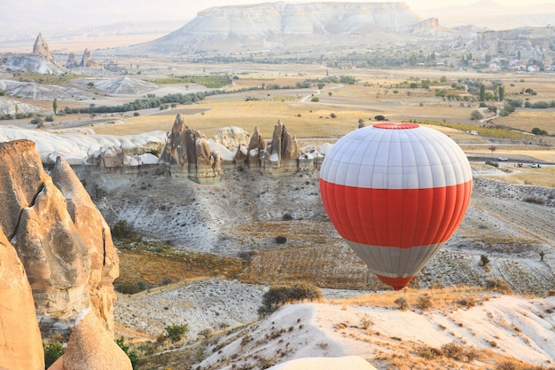 Selective focus on hot air balloon flying over the valley at cappadocia. hot air balloons are traditional touristic attraction in cappadocia.