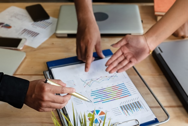 In selective focus human hand with pen pointing at business paper chart