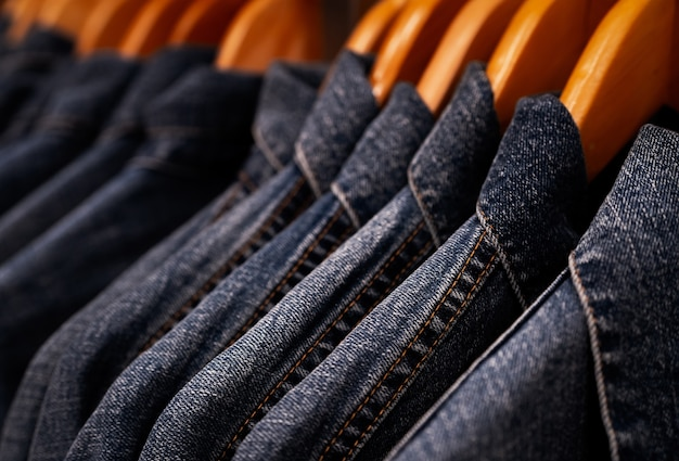 Selective focus on jacket jeans hanging on rack in clothes shop. denim jeans with jeans pattern.
