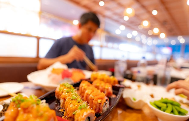 Selective focus on japanese food in a japanese restaurant. salmon sushi on a plate with blurred man eating japanese food with chopsticks in the restaurant. healthy asian food. salmon sushi menu.