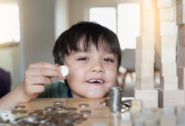 테이블에 동전의 흐릿한 전경으로 웃는 얼굴로 그의 손에 돈 동전을 들고 선택적 초점 아이.
