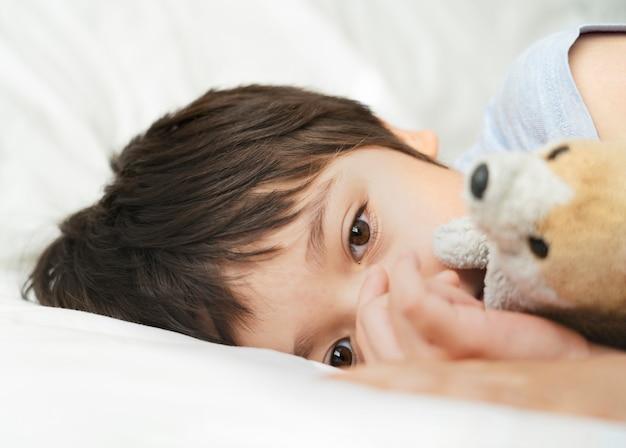 セレクティブフォーカス子供がベッドに横になっている、眠そうな子供がベッドの部屋で朝目を覚ます、小さな男の子がベッドに横になって深く考えている、子供のヘルスケアまたは幼児の睡眠の問題
