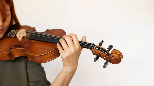 In selective focus of lady hand holding and pressing finger on string,show how to play acoustic instrument,blurry light around