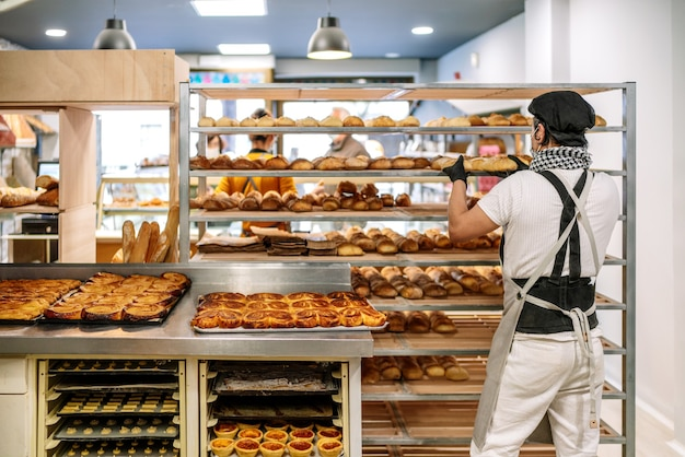 Selective focus of latino baker shelving freshly baked bread with a protective face mask