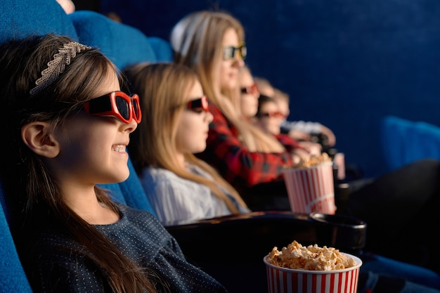 Selective focus of laughing child wearing 3d glasses, eating popcorn and watching funny movie. cute little girl enjoying time with friends in cinema
