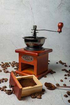 Выборочный фокус. ручная ретро мельница для кофе в зернах. темное дерево на светло-сером фоне. с кафе, написанным металлическими буквами
