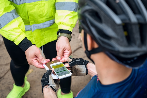선택적 초점, 산악 자전거 운동선수는 자전거 경주장에서 전화로 예방 접종 인증의 건강 여권을 보여주고 코로나바이러스 예방 접종을 받았음을 증명합니다. covid-19 전염병 동안 스포츠.