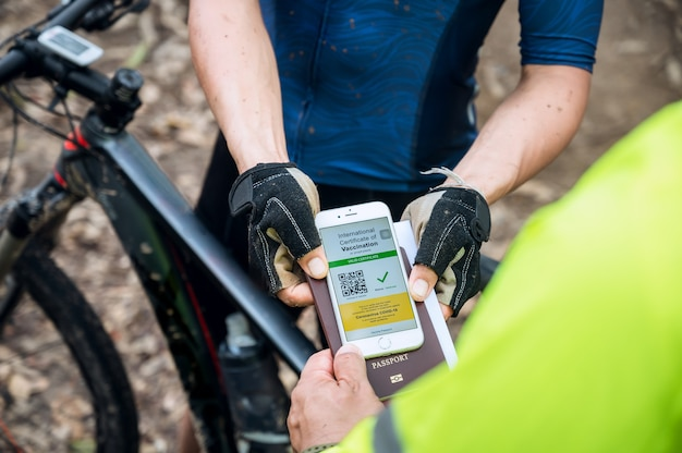 Selective focus, mountain bike athlete show health passport of vaccination certification on phone at bicycle race track, to certify have been vaccinated of coronavirus. sport during covid-19 pandemic.