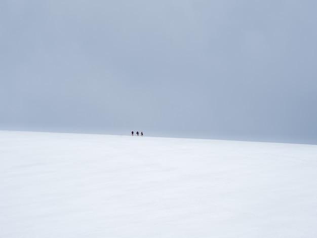 선택적 초점입니다. 등산객은 눈 덮인 언덕 꼭대기에 온다. 팀워크와 승리, 어려운 상황에 있는 사람들의 팀워크. 산 정상까지 오르는 험난한 여정.