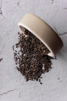 Selective focus, natural black leaf tea. brewing in a clay bowl. vertical angle, macro. on a light background. for menus and cafes