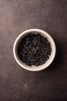 Селективный фокус заваривания натурального черного листового чая в макросе вертикального угла глиняной миски на темном фоне ...