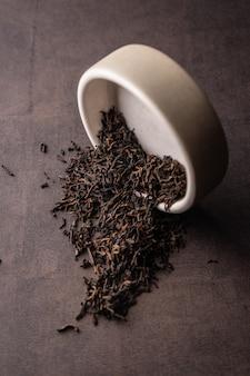 セレクティブフォーカス、ナチュラルブラックリーフティー。粘土のボウルで醸造。頂角、マクロ。暗い背景に。メニューやカフェ用