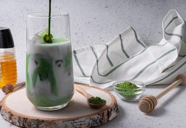 Селективный фокус, натуральный напиток матча со льдом, латте с молоком. чай в высоком стакане