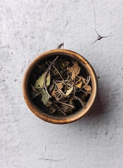 Selective focus, natural green leaf tea. brewing in a clay bowl. vertical angle, macro. on a light background. for menus and cafes