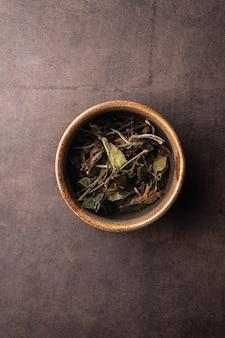 暗い背景の粘土ボウル垂直角度マクロでのセレクティブフォーカスナチュラルグリーンリーフティー醸造...