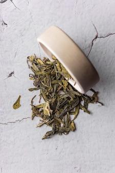 Селективный фокус заваривания натурального зеленого листового чая в макросе вертикального угла глиняной миски на светлом фоне ...