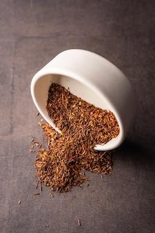 Селективный фокус заваривания натурального красного листового чая в макросе вертикального угла глиняной миски на темном фоне ...