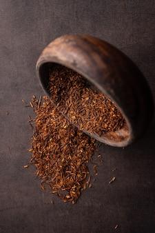 Селективный фокус заваривания натурального красного листового чая в макросе вертикального угла деревянной чаши на светлом фоне ...