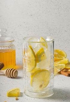 Селективный фокус, натуральные витамины, высокий стакан со льдом для воды, прозрачная банка с медом и нарезанные дольками лимона на светлом фоне
