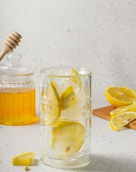 Selective focus, natural vitamins, high ice glass for water, transparent jar with honey and sliced lemon slices on a light background
