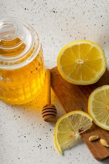 Selective focus, natural vitamins, transparent jar with honey and sliced lemon slices on a light background