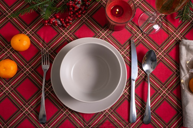 Selective focus. new year's table setting with a red checkered tablecloth and a high champagne glass. low key. postcard
