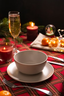Selective focus new years table setting with a red checkered tablecloth and a high champagne glass l...