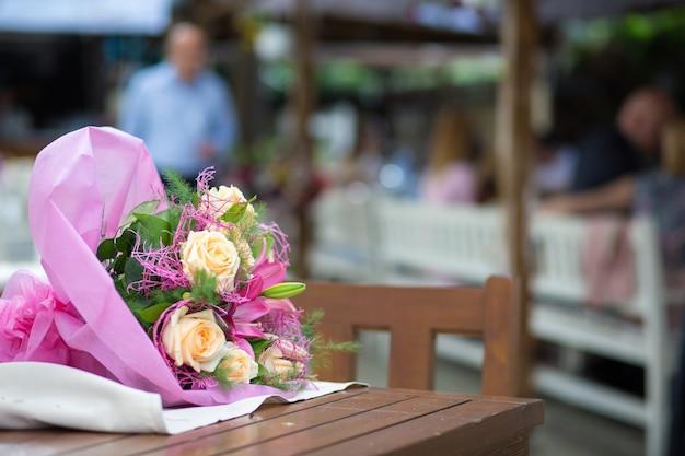 나무 테이블에 아름다운 꽃다발의 선택적 초점