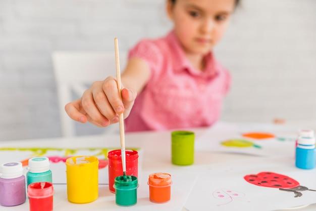 白い机の上のカラフルなボトルに絵筆を挿入する女の子の選択と集中